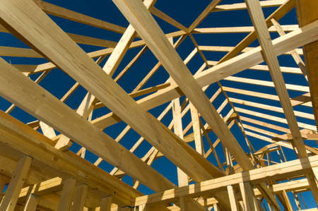 4s: New home under construction with wood, trusses and supplies against blue sky