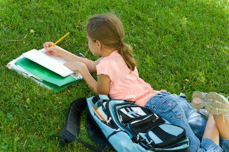 bookbag: Young girl in park doing school work Stock Photo