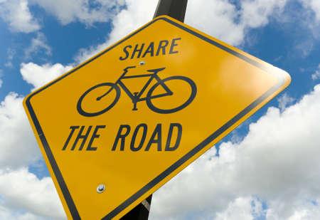 achtung schild: Angesichts der breiten Ange Fahrrad Vorsicht Zeichen wih die Worte - die Stra�e vor einem blauen Himmel bew�lkt Lizenzfreie Bilder