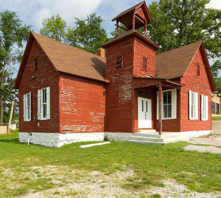 school house: Old roja casa con la escuela de pintura de viruta y los �rboles agianst cielo azul  Foto de archivo