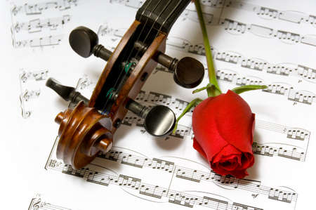 A violin peg-head, red rose and sheet music 版權商用圖片