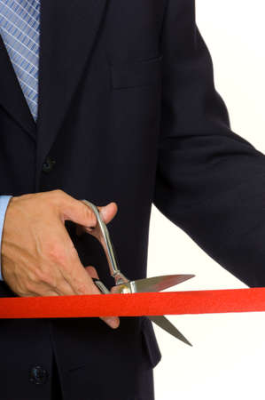 Closeup of a mans hand in a blue business suit cutting a red ribbon with shiny scissors- focus on ribbon Stock Photo - 1544392