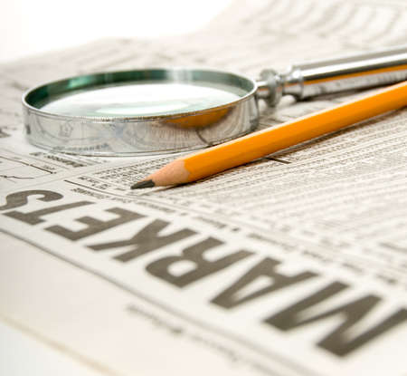 stock listing: Newspaper open to market section wit tools for research, pencil and magnifying glass