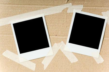 Twee foto's bevestigd met plakband op een kartonnen doos Stockfoto