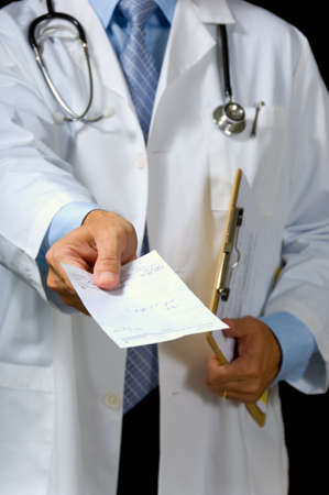 prescribe: focus on thumb of hand giving prescription, all patient or doctor info has been removed from form except the scribbling indicating medication Stock Photo