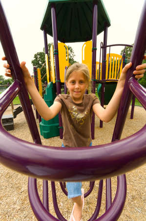 extreme angle: YOung girl playing at the playground on cloudy day- shot with an extreme wide angle lens