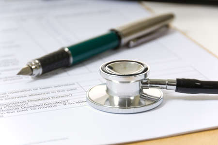 health questions: Doctors clipboard with stethoscope lying on top with a fountain pen Stock Photo