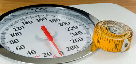 inches: Bathroom scale with large dial and tape measure.  Theme of dieting or living healthy Stock Photo