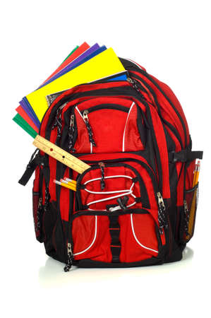 batoh: Red backpack overflowing with school supplies including pencils, rulers, folders and books