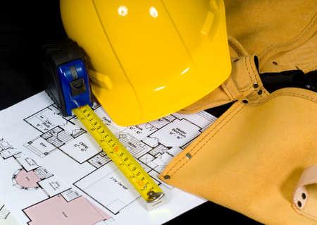 Home bouw items icluding een helm een leren riem instrument een meetlint en plattegronden Stockfoto