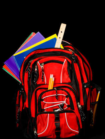 bookbag: Red backpack overflowing with school supplies including pencils, rulers, folders and books