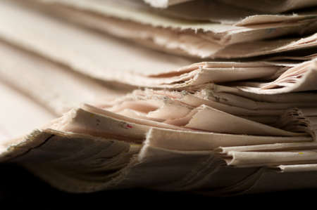 Stack of newspapers for use as a background focus is on the right hand side and decreases quickly toward the left Stock Photo