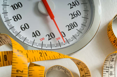 Bathroom scale with large dial and tape measure.  Theme of dieting or living healthy Stock Photo - 1559150