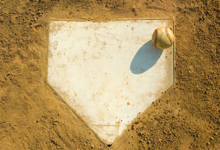 dirt: Old baseball on home plate surrounded by dirt, plenty of copy space Stock Photo