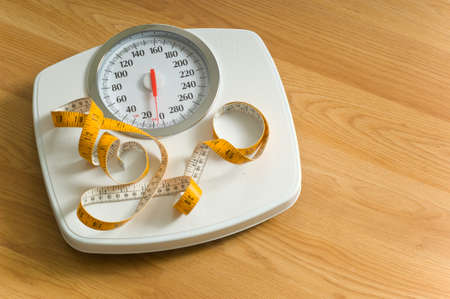 Bathroom scales with a large dial and a tape measure on a wooden floor with area to the left for copy  Stock Photo