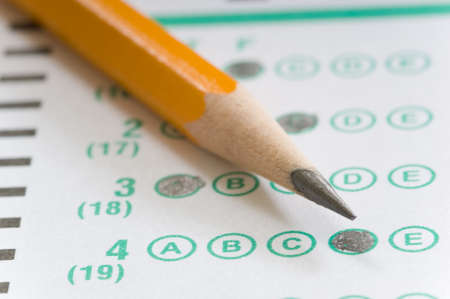 Yellow pencil on multiple choice test computerized answer sheet - focus is on the letter D in answer number 4