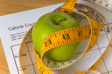 Items that would be associated with dieting or losing weight, including a tape measure, an apple, and a calorie counting chart, foucs on top of apple, calorie chart is blurry