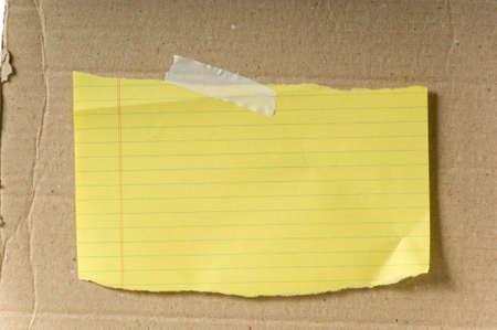 Gele blanco papier geplakt op een stuk karton met een kopie ruimte - achtergrond