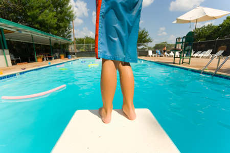 apprehension: Young boy standing on the end of a diving board at a swimming pool Stock Photo