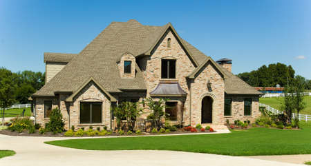 Beatuful two story home with  landscaped yard against blue sky Stock Photo