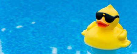 黄色の色合いで青い水、コピーのためのスペースの上のゴム製のアヒル