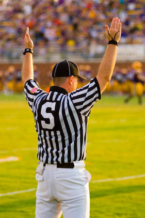 referees: A Football Official signaling football and a game of American Football Stock Photo