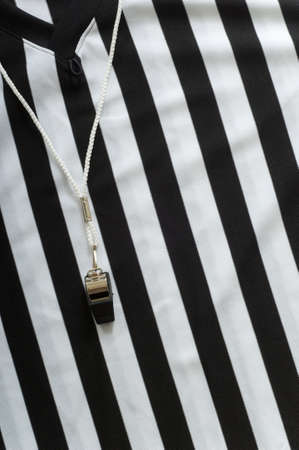 unifrom: black and white striped referee jersee with a whistle to the left, copy space on the right hand side of image