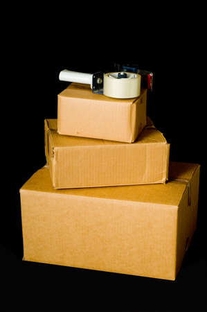 delivery service: Brown corrugated shipping boxes on a black background with a tape gun