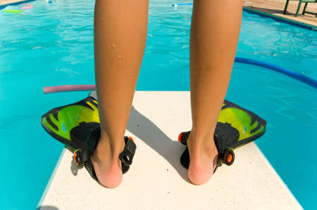 flippers: Child standiing with flippers on the end of a diving board at a swimming pool