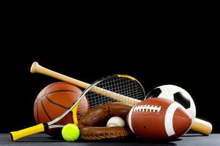 balones deportivos: Una variedad de material deportivo en un fondo negro incluida una de f�tbol americano, un bal�n de f�tbol, el b�isbol, un bate de b�isbol, una cancha de tenis Raquet, una pelota de tenis, baloncesto y un