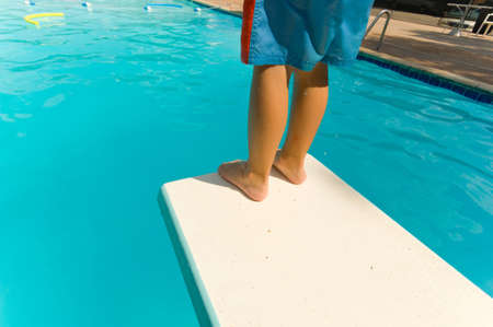 apprehension: Young boy standing on the end of a diving board at a swimming pool - seems to be a little apprehension