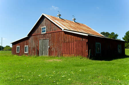 Old red barn against blue sky with green grass in front photo