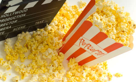 entertainment industry: Movie and entertainment industry items, including a box of popcorn a movie clapboard and a strip of 35mm film Stock Photo
