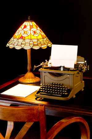 novelist: Old, antique, vintage, typewriter in writers or authors area with lamp on black background