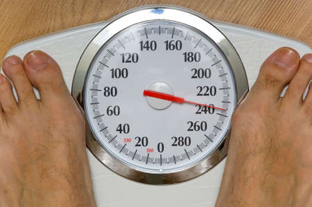 heavy: Heavy man on scale with large dial weighing 230 pounds, theme of dieting or losing weight Stock Photo