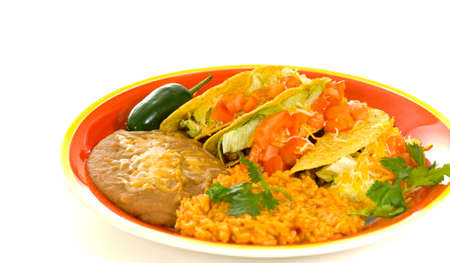 jalapeno pepper: A plate of sterotypical Mexican food including tacos, bean, rice, cilantro and a green jalapeno pepper