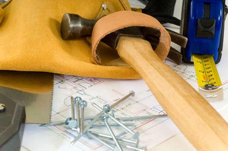 Klusjesman of bouw werknemer items met inbegrip van een instrument leren riem, een hamer, een zaag, nagels, floor een meetlint en een huis plan Stockfoto