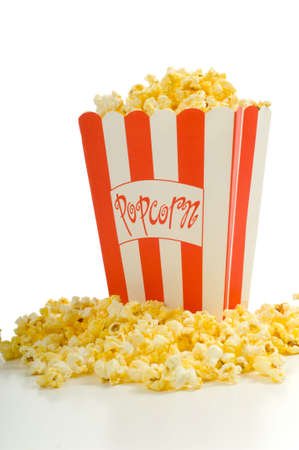 popped: Movie popcorn on white background with red striped box and freshly popped popcorn on white background