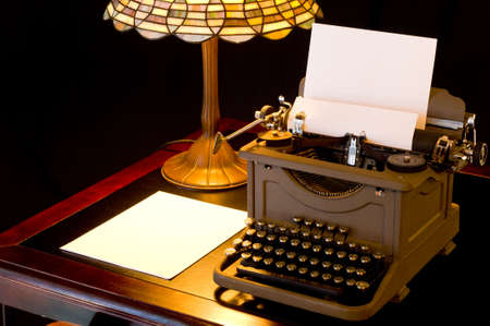 Old, antique, vintage, typewriter in writers or authors area with lamp on black background photo