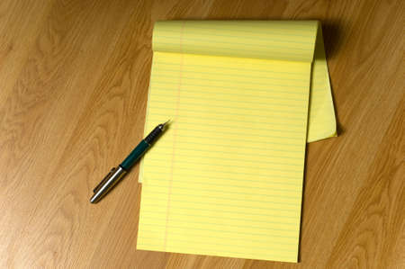 legal pad: A blank, yellow legal pad on a brown wooden desk or floor with a writing pen on the edge, add your own copy