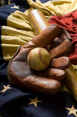 gant de baseball: Cru, articles antiques de base-ball comprenant une vieille mitaine en cuir ou gant et batte de base-ball en bois et antiquit� semblant l�tamine am�ricaine de drapeau