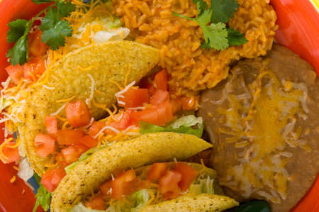 кинза: A plate of sterotypical Mexican food including tacos, bean, rice, cilantro and a green jalapeno pepper