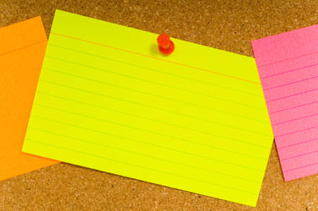 notecard: Bright, blank neon colored notecards on brown corkboard or bulletin board with plastic pushpins, space for copy