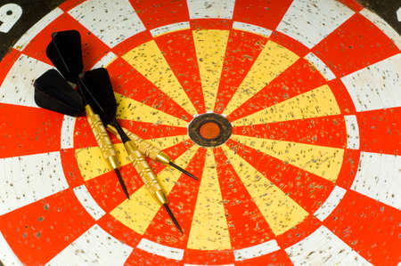 Dartboard with several darts lying on top of board