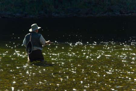waders: Lone pescador con botas para la pesca con ca�a y la pesca en un r�o hermoso d�a soleado en