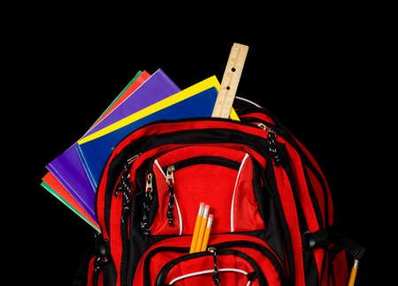 A red school backpack stuffed full of school supplies including folders, pencils, notebooks and a ruler all on a black background with copy space