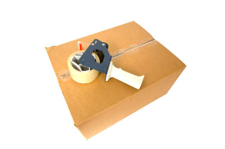 packing tape: Brown, corrugated cardboard shipping box with packing tape on top on white background