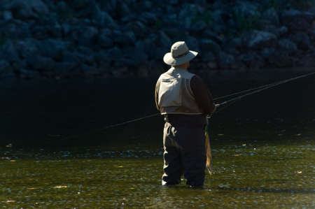 fishing pole: Lone fisherman with fishing pole and waders fishing in a river on beautiful sunny day