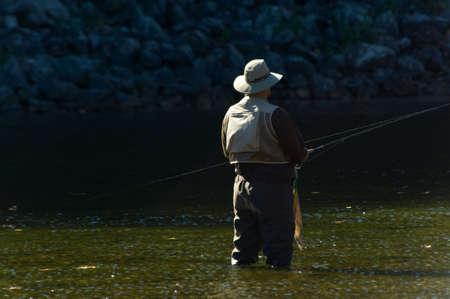 waders: Lone pescador pesca con ca�a y botas de pesca en un r�o hermoso en los d�as soleados  Foto de archivo