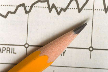 charting: A yellow wooden pencil lying on top of a stock chart or chart showing a upward trend, illustrates studying the markets or business charts etc
